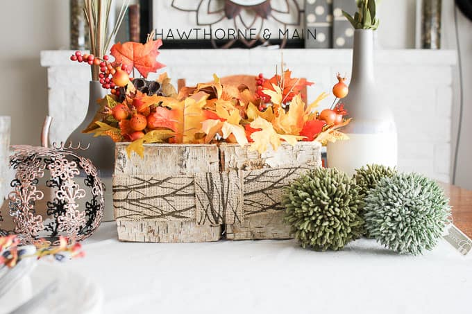 fall leaf centerpiece with burlap ribbon on the table.