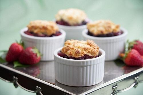 Berry cobbler in white mini ramekins with strawberries beside them.