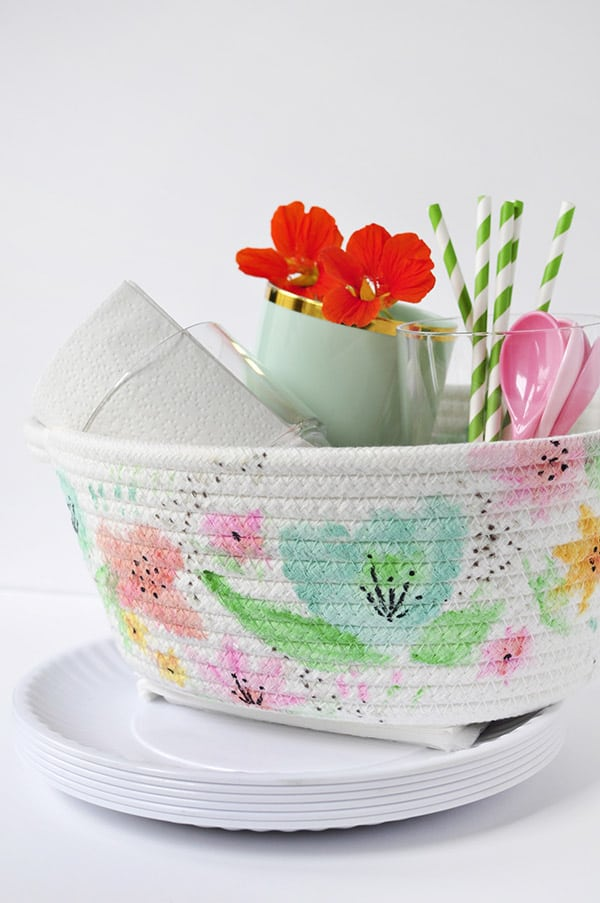 A basket painted white with watercolour flowers.