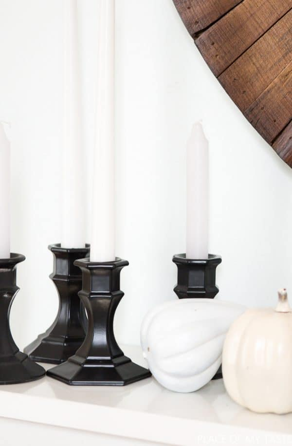 black candle holders with white pumpkins and a wood wall hanging