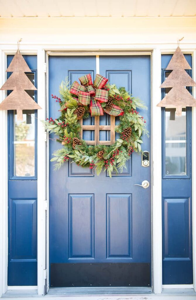 blue front door with large fir wreath with pinecones and wood tree cut outs on wither side