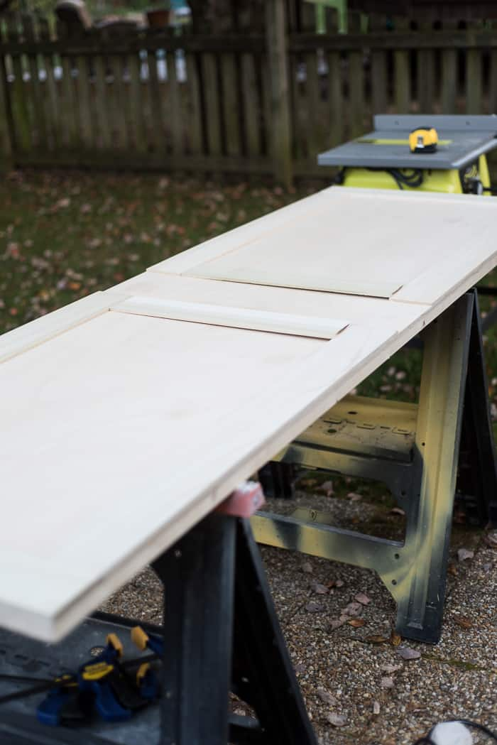Learn how to make this modern DIY sliding barn door. It's easy and adding a sliding barn door will save you space in any of your rooms.