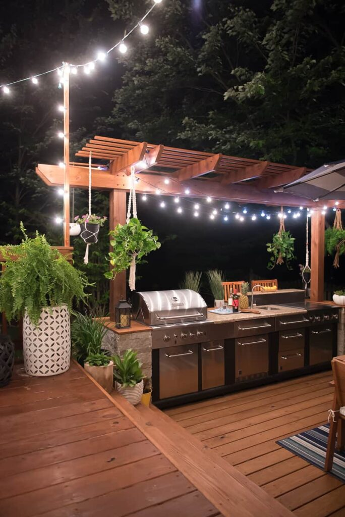 Amazing Outdoor Kitchen With String Lights At Night.