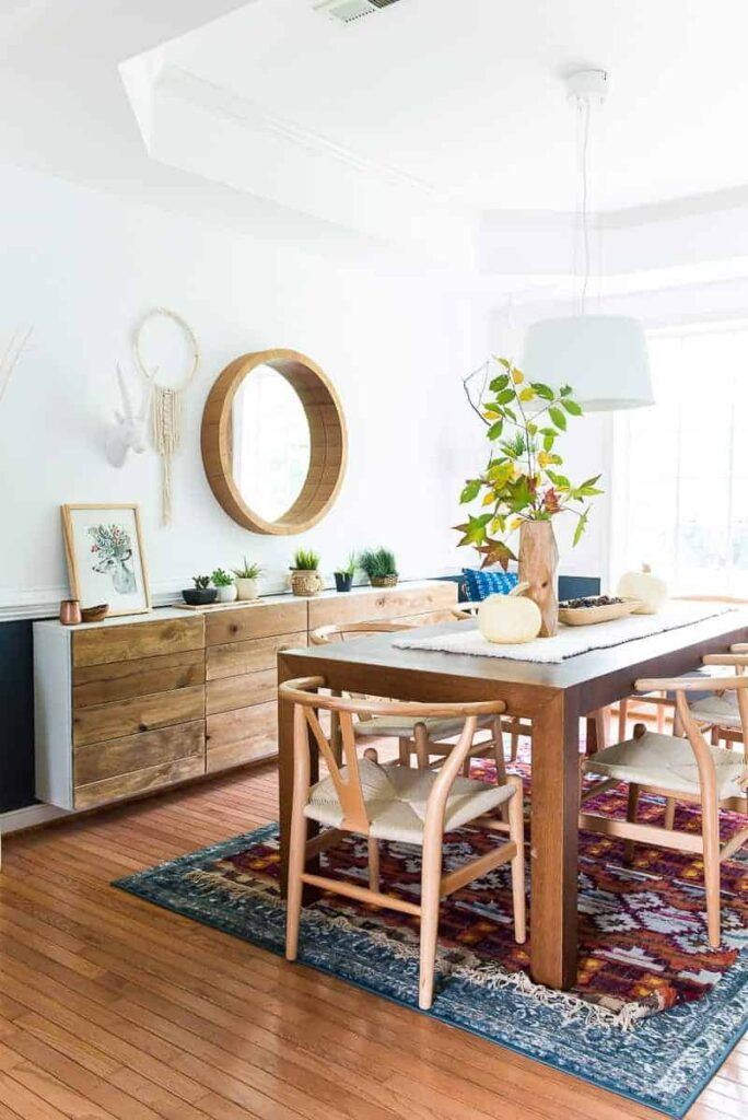 dining room with reclaimed wood buffet and large wood table- fresh branches and white pumpkinson the centerpeice
