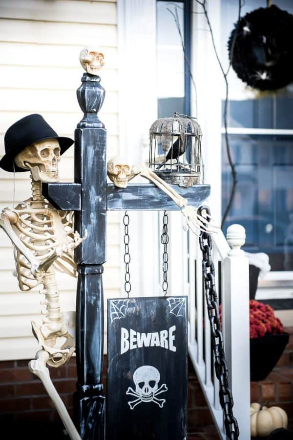 skeleton in the yard with beware sign for halloween