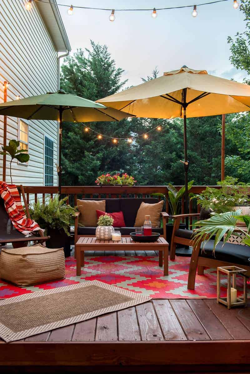 The patio set and umbrellas and rugs all highlighted with the string lights as the sun sets