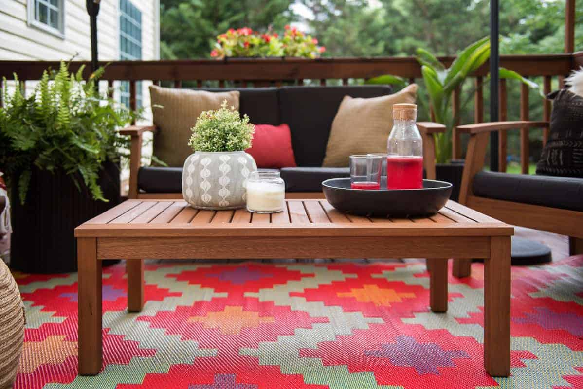 Beautiful multi colored red rug and black cushioned teak conversation set