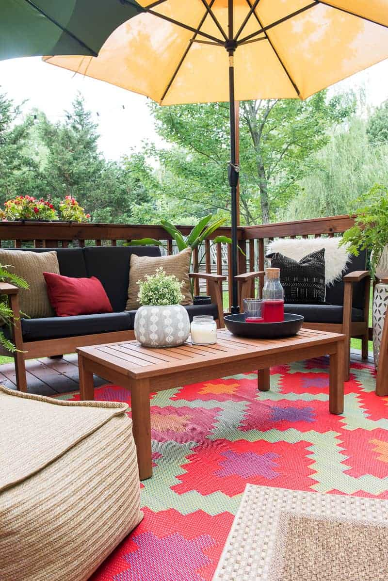 outdoor patio set with two overlapping umbrellas and layered rugs