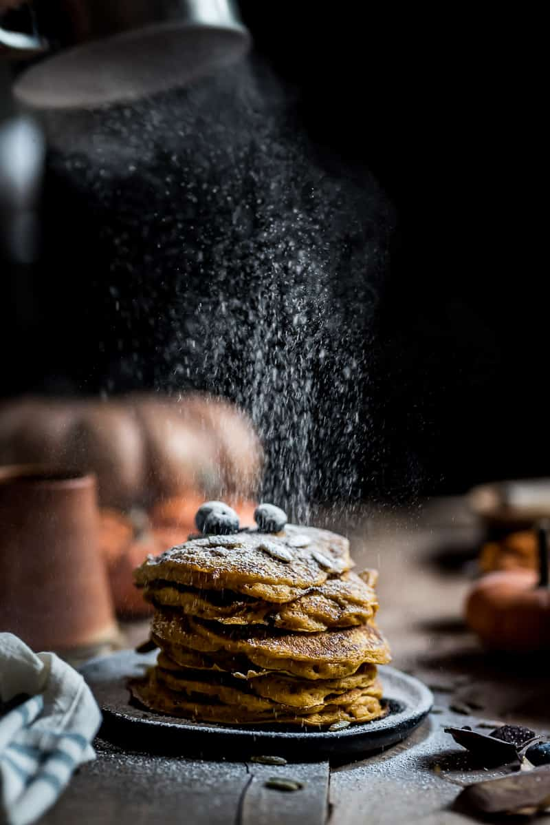 Pumpkin pancakes getting a dusting of confectioners sugar