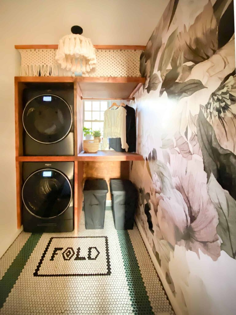 Small Laundry Room makeover. I love the stacked washer and dryer, the dramatic peel and stick wallpaper and penny tiles in this laundry room. The DIY Shelving around washer and dryer is brilliant . And talk about that macrame curtain...! Wow. Such a great laundry room makeover.