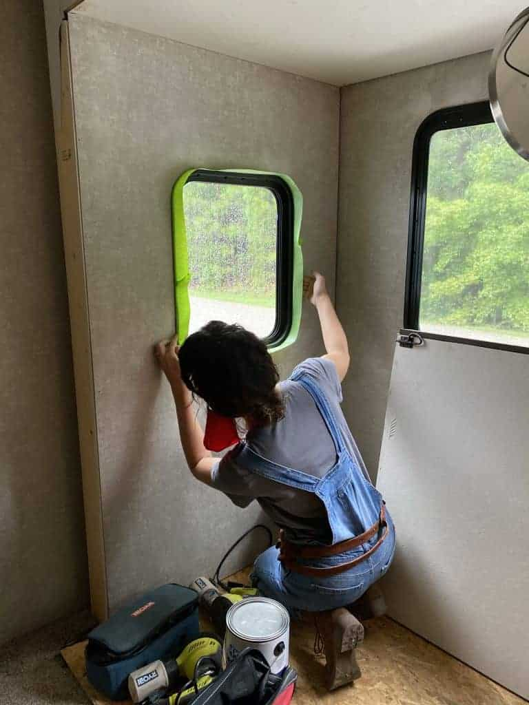 Tape the windows in a camper before painting the walls.